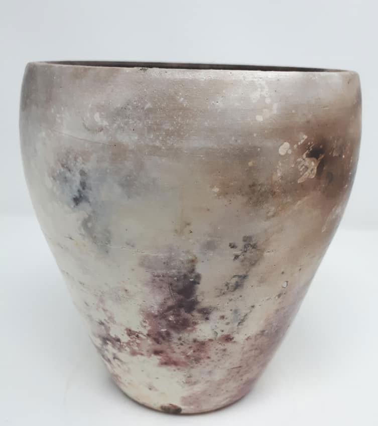 Pit fired pot using local seaweed and fruit skins for effects
